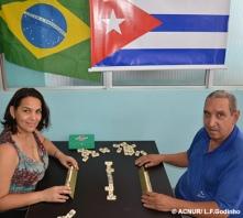"""Loyda e Guilhermo deixaram Cuba com seus dois filhos devido às atividades políticas dele. A família chegou ao Brasil em 2009 com alguns pertences, entre eles um dominó. """"Jogar dominó nas horas livres é tipicamente cubano e fazemos isso todo domingo, com outros amigos cubanos que vivem aqui"""", afirma Loyda. """"Nosso dominó tem a marca de uma famosa cerveja cubana, o que nos faz lembrar do nosso país"""", completa Guilhermo."""
