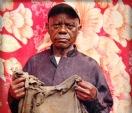"""Msafiri Tawimbi deixou a República Democrática do Congo com sua família em 1996. Antes de chegar a Tanzânia, onde se refugiariam, eles caíram na emboscada de um grupo de soldados. Sua esposa foi morta e sua filha de dois anos ficou gravemente ferida. O objeto que restou desse episódio foi uma camiseta rasgada, que usava durante a fuga. """"Ela me lembra de tudo o que minha família passou"""", diz"""